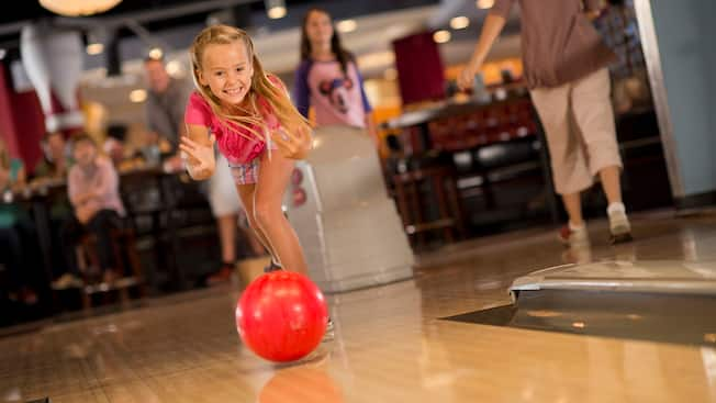 A smiling young girl bowls with both hands while her family watches in the background at Splitsville Luxury Lanes in Downtown Disney Area
