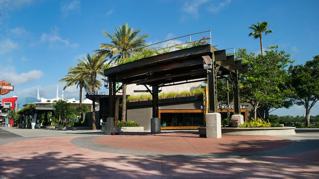 El área de presentaciones de Sunshine Highline en frente de Starbucks West Side en Disney Springs con una vía de tren elevada