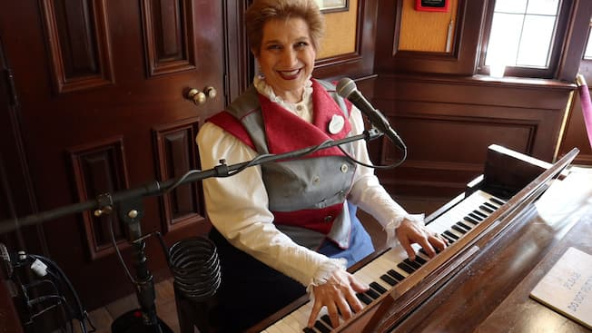 A Cast Member smiles while playing a piano in front of a microphone