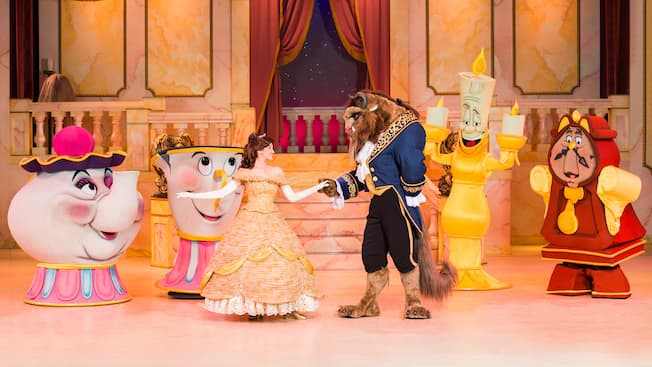 Beast dança com Belle no palco, enquanto Lumiere, Cogsworth, Mrs. Potts e Chip assistem encantados