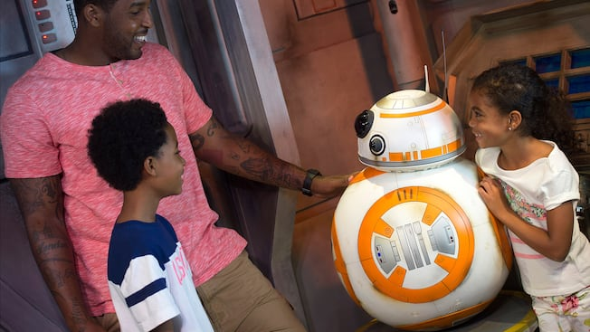Un padre con su hijo y su hija conocen a BB-8, el leal droide de la película Star Wars: The Force Awakens, en el sector de seguridad de Star Wars Launch Bay