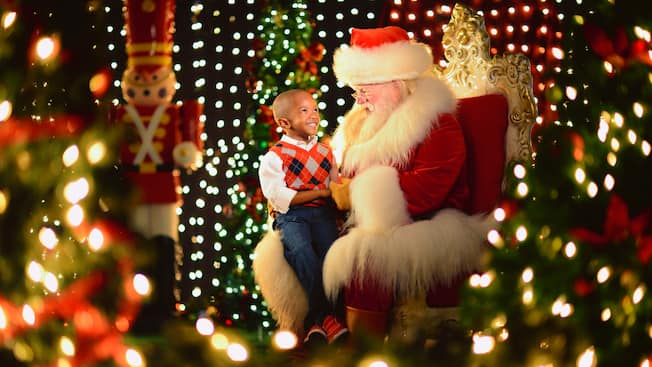 A small boy smiles while sitting on Santa's lap