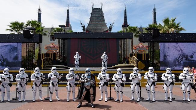 Na Animation Courtyard do Disney's Hollywood Studios, a Captain Phasma com seu blaster a postos e uma fileira de Stormtroopers Imperiais em guarda em frente a mais 2Stormtroopers Imperiais enfileirados em um palco ao fundo