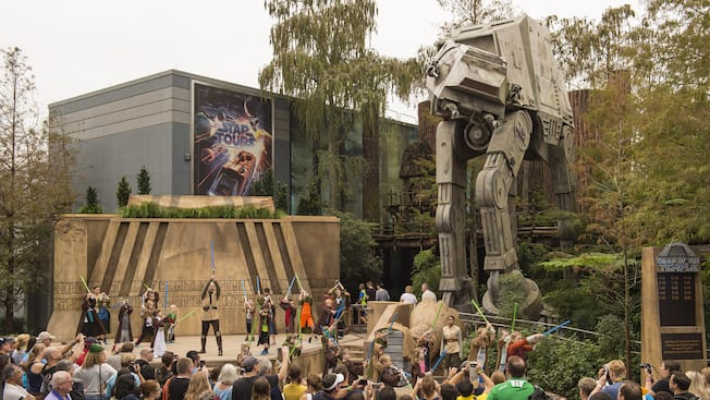 Jedis y niños se divierten con sables de luz cerca de una multitud de espectadores, un vehículo AT-AT y un letrero que dice Star Tours