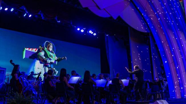 Una proyección de Buzz Lightyear de la exitosa serie de películas Toy Story detrás de la orquesta