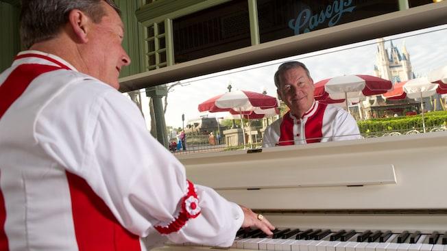 Un pianiste joue du piano au Casey'sCorner avec le château de Cendrillon, se reflétant dans un miroir