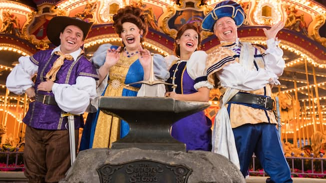 4 performers in medieval attire laugh near an anvil with a sword stuck into it with a sign that reads The Sword in the Stone