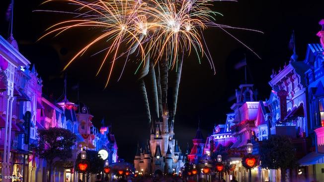 Fogos de artifício do Castelo da Cinderela iluminam a noite em uma rua com luminárias temáticas do Mickey Mouse