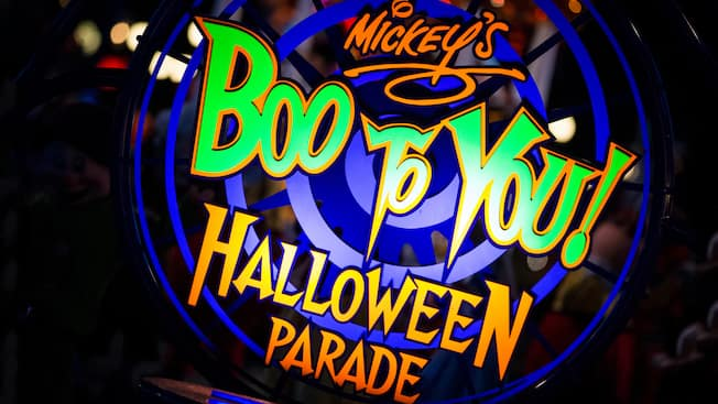 Uma placa bem iluminada anuncia: Desfile de Halloween 'Mickey's Boo-To-You!'