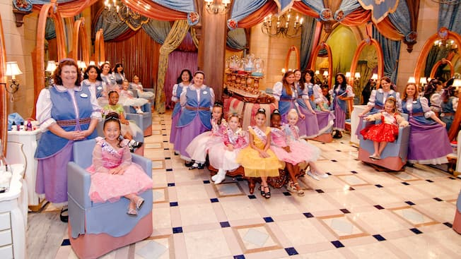 Girls dressed as princesses and their hair stylists at Bibbidi Bobbidi Boutique at Downtown Disney area