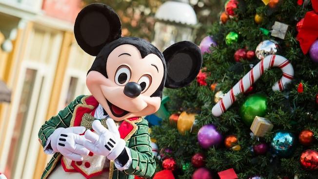 Mickey Mouse se tient près d'un arbre de Noël