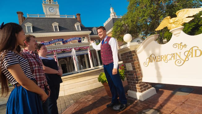 Un guide parle aux visiteurs qui l'accompagnent à l'extérieur du pavillon American Adventure du World Showcase à Epcot au Walt Disney World Resort