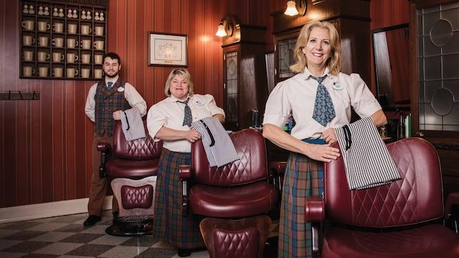 2 mulheres e um homem posam com aventais ao lado de cadeiras de barbearia