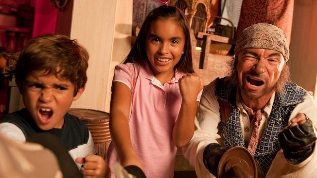 Un niño y una niña contraen los puños y dan un grito sano mientras una espada de pirata los lidera