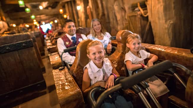 A Cast Member rides with a family in a roller coaster