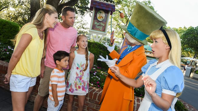 A Family Speaks With The Mad Hatter And Alice Near Sign That Reads Tea