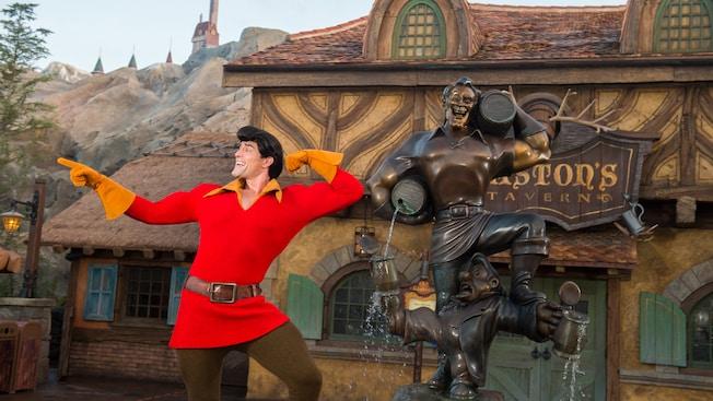 Gaston exhibe su fuerza mientras posa con orgullo junto a su estatua fuera de Gaston's Tavern en Fantasyland