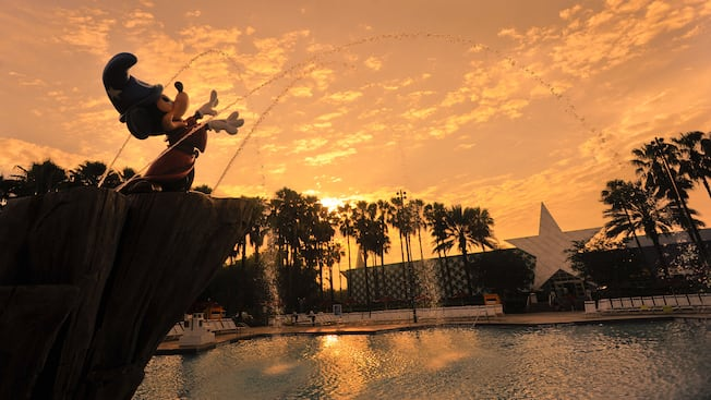 Silhueta contra o pôr do sol da Sorcerer Mickey Fountain na Fantasia Pool no Disney's All-Star Movies Resort