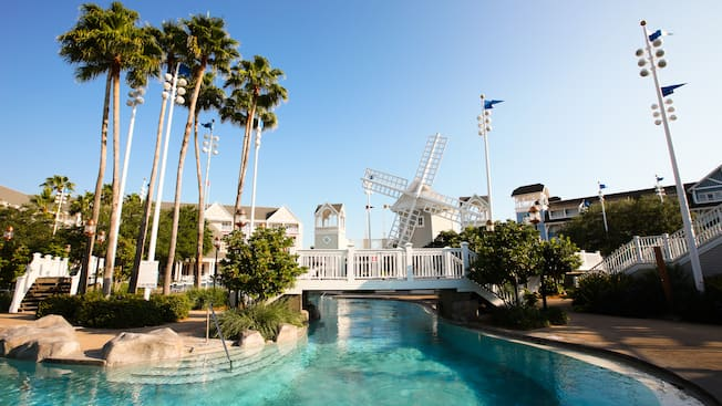 Pools At Disney S Beach Club Resort Stormalong Bay Pool Area Featuring A Windmill And An Island Accessible By 2 White Bridges