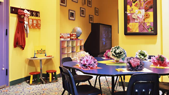 Uma área de lazer infantil com mesa de artesanato, brinquedos e uma TV de tela grande