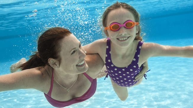 A smiling mother has an arm around her daughter's waist as they swim underwater in a pool