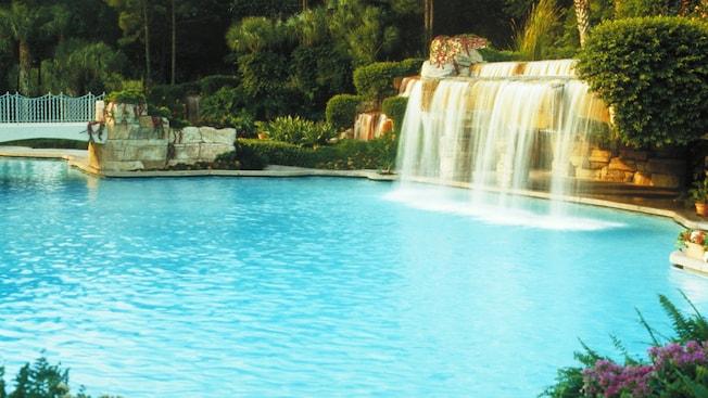 Piscine bleu azur avec chute d'eau encadrée d'une végétation luxuriante à l'hôtel Walt Disney World Swan