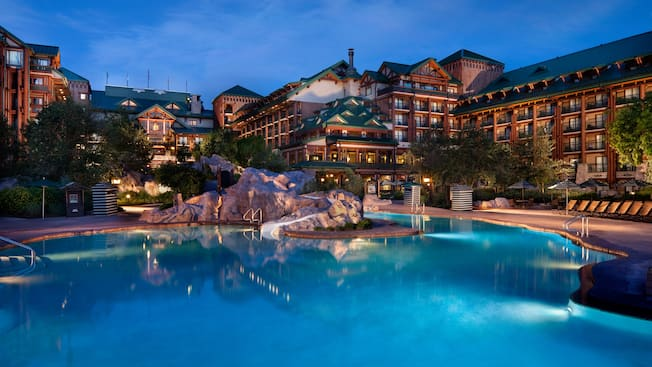 A pool area with artificial boulders, lounge chairs, parasols and a waterslide inside Disney's Wilderness Lodge