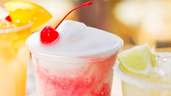 Uma Dawa Colada gelada cercada por 2 outras bebidas especiais no Dawa Bar