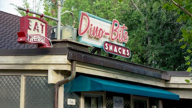 Una cena rústica con luces de neón y un letrero de Dino-Bite Snacks entre árboles y demás vegetación