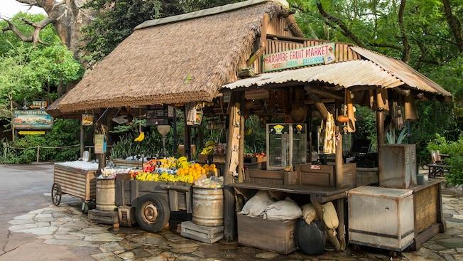 Un rústico kiosco llamado Harambe Fruit Market que exhibe fruta fresca, bolsas de papas fritas y snacks variados