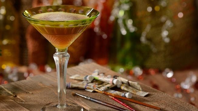 Un elegante vaso de martini lleno con un cóctel Night Monkey en una mesa al lado de tubos de acuarelas y pinceles