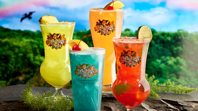 Four different cocktails over ice in Rainforest Cafe logo glasses with fruit garnishes