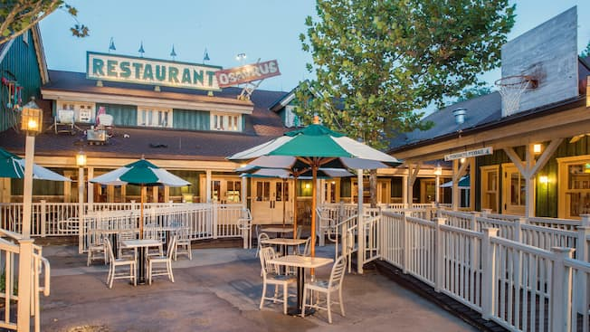 Animal Kingdom dining guide: An outdoor dining area at Restaurantosaurus with novelty patio décor, umbrellas, chairs and tables