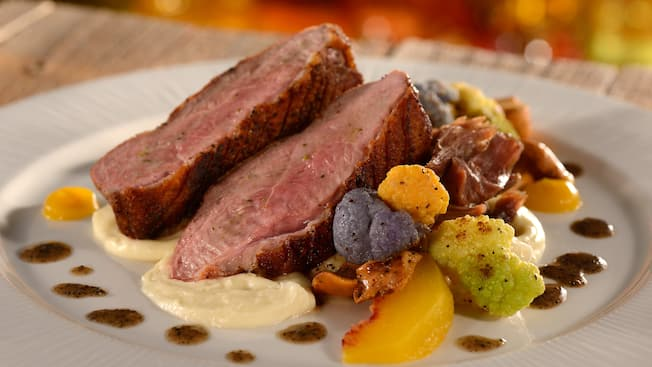 A plate containing slices of roast duck leg atop a bed of puree beside florets of cauliflower and a wedge of cooked peach
