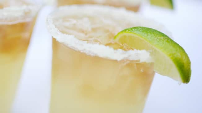 An icy margarita garnished with a slice of lime and served in a glass with a lightly salted rim