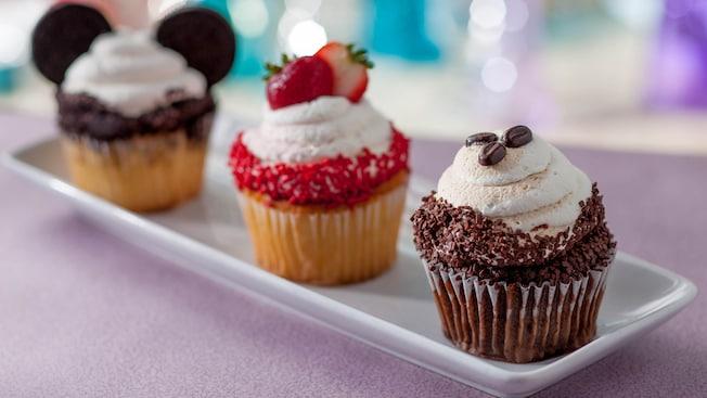 3 cupcakes en una bandeja, uno con orejas de Mickey