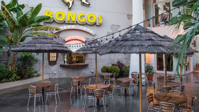 Outdoor dining under thatched-roof umbrellas at Bongo's Cuban Café Express in Downtown Disney area.