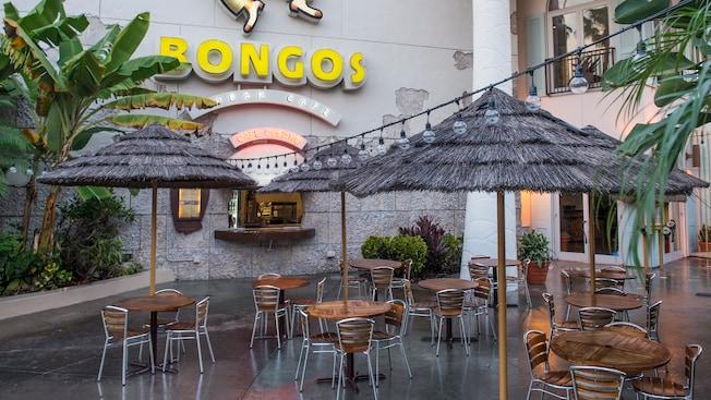 Restaurante al aire libre con sombrillas de paja en Bongo's Cuban Café Express, en el área de Downtown Disney.