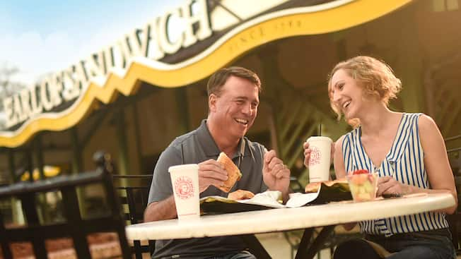 A couple sits at an outdoor table enjoying their Earl of Sandwich meals
