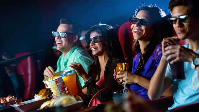 Guests enjoy food, drinks and a movie inside of the AMC Disney Springs 24 Dine In Theatre