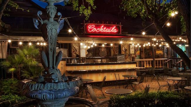 Fontaine en forme de Sphinx près des tables de la terrasse et bar éclairé par une enseigne au néon indiquant «Cocktails»