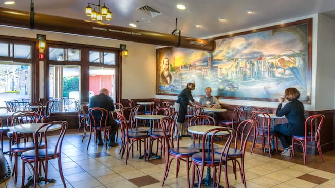 Un área de comidas con sillas, mesas, un mural y Huéspedes siendo atendidos por una camarera