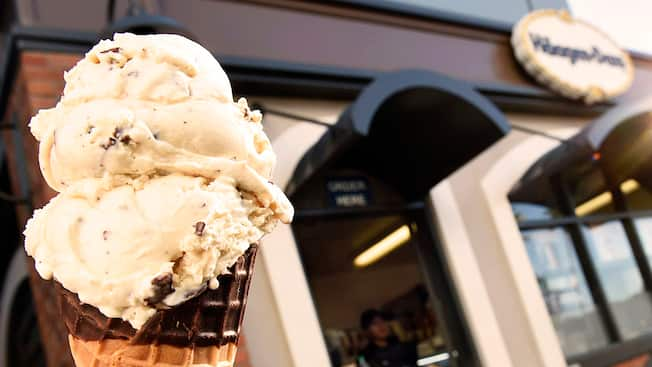 A chocolate dipped cone with 3 scoops of vanilla chocolate chip ice cream is held in front of the exterior of Haagen Dazs