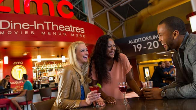 Amigos apreciam as bebidas no MacGuffins, dentro do cinema AMC Disney Springs 24