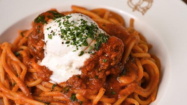 Espagueti a la boloñesa cubierto con queso y hierbas