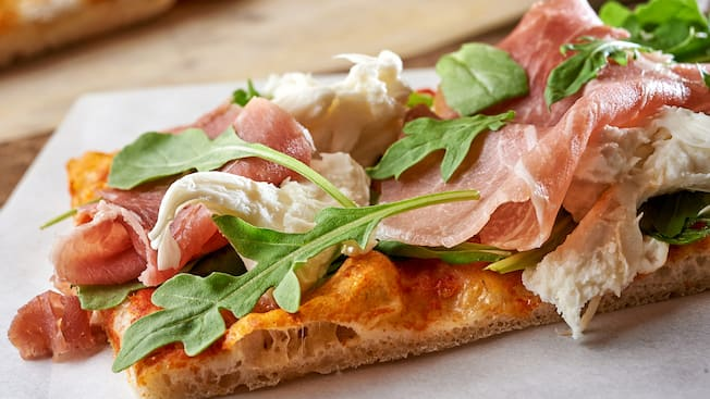 Flatbread topped with prosciutto, mozzarella and arugula