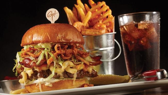 Una hamburguesa grande de carne de ternera y macarrones con queso, servida con papas fritas y un refresco