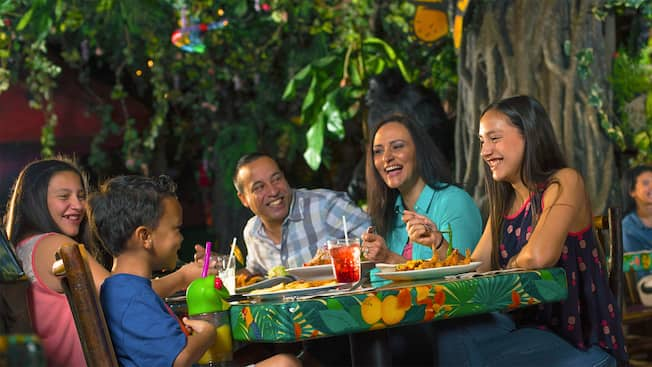 Una familia de 3 integrantes cena en el Rainforest Café, en Disney Springs Marketplace