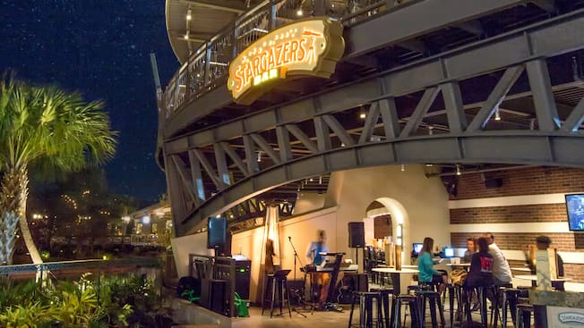 The Stargazers Bar open air patio at Planet Hollywood Observatory at night with Guests seated at tables and a musician setting up