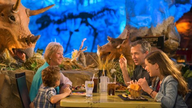 Menina e seu pai aproveitam batata frita em formato de waffles, sentados à mesa com decoração temática de dinossauros ao fundo